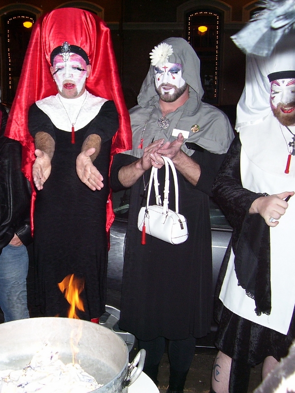 Left to right: Sister Polly Amorous, Postulant Ruth Les'Bitch, and Sister Krissy Fiction look on as the veil burns.
